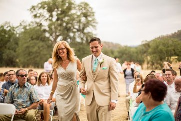 My handsome groom walking down the aisle with his mother.